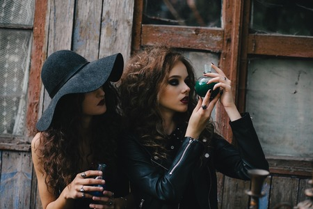 mystic place: Two vintage witches perform magic ritual, with elixir in hand on the eve of Halloween
