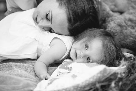 Divirtiéndose. Bastante joven madre y su pequeña hija miente en la cubierta en el parque y que tienen comida campestre. Foto de archivo