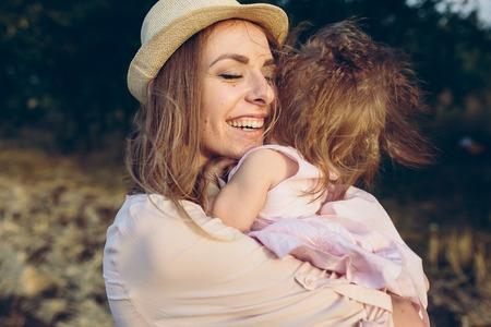 Madre e hija riéndose juntos al aire libre