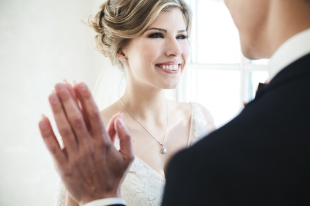 facing each other: the bride and groom facing each other on white background