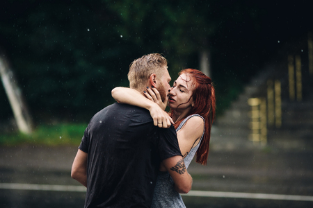 love in rain: beautiful couple kissing outside in the rain