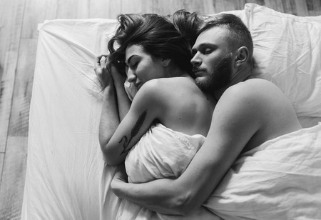 man and woman sex: красивая пара вместе лежал на кровати Фото со стока