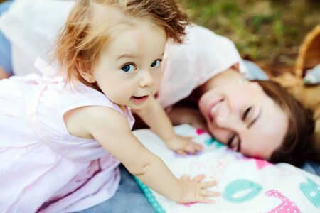 portrait of woman: Having fun. Pretty young mother and her little daughter lying on cover in park and having picnic.