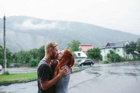love in rain: beautiful couple hugging on outside in the rain