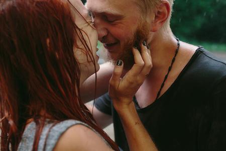 uomo sotto la pioggia: bella coppia abbracciare al di fuori sotto la pioggia