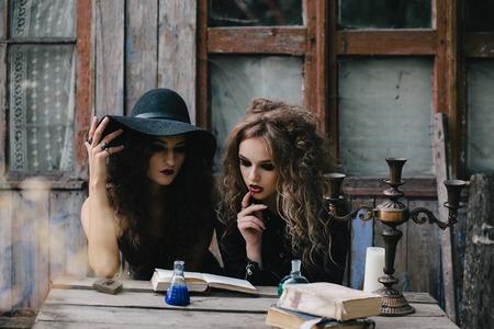 elixir: Dos brujas vendimia realizan ritual mágico, con el elixir de la mano en la víspera de Halloween de