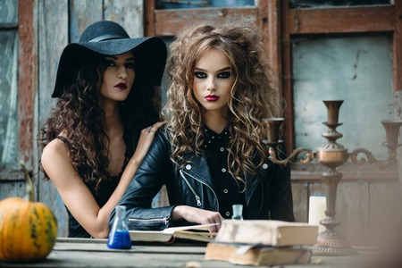 Two vintage witch sitting at the table in an abandoned place on the eve of Halloween