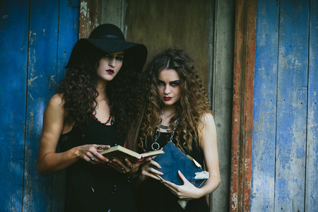 Two vintage witch reading a book on the eve of Halloween in front of an abandoned house