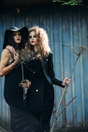 sibyl: two vintage women as witches, posing in front of an abandoned house on the eve of Halloween