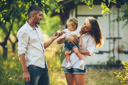 Parents with baby enjoying picnic on a farm with apple and cherry trees.