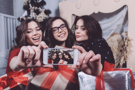 home party: Beautiful girl photographed themselves on the phone on the background of Christmas gifts. Decorative vintage apartment. Stock Photo