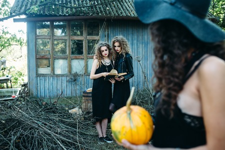 sibyl: three vintage women as witches, pose in front of an abandoned building on the eve of Halloween