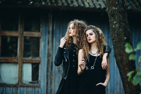 enchantress: two vintage women as witches, posing beside an abandoned building on the eve of Halloween