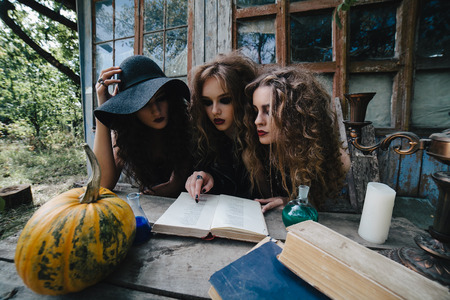 Three vintage witches perform magic ritual, at the table, reading a magical book on the eve of Halloween Stock Photo