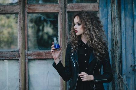 elixir: Bruja del vintage realiza ritual mágico, con el elixir de la mano en la víspera de Halloween de