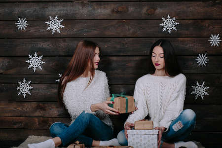 unpacked: Two pretty young funny girls friends smiling and having fun, holding holiday presents Stock Photo