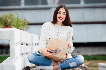 unpack: Beautiful girl sitting on a bench and holding in her hands a gift