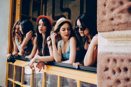 italy street: five beautiful young girls look out from the window Stock Photo