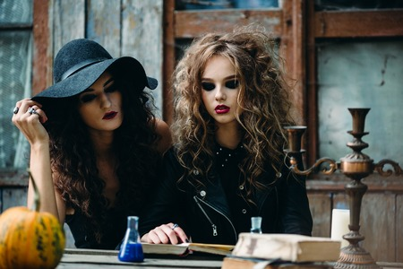 sibyl: Two vintage witch sitting at the table in an abandoned place on the eve of Halloween
