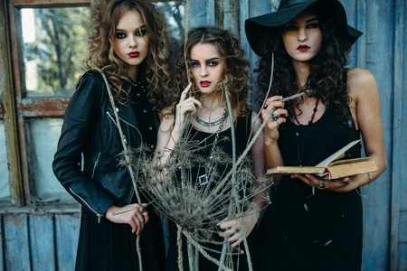 sibyl: three vintage women as witches, pose in front of an abandoned building with books in hand on the eve of Halloween