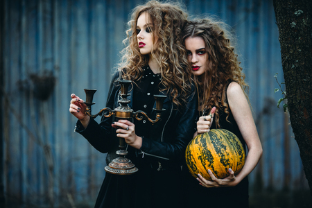 evil woman: two vintage women as witches, posing in front of an abandoned house on the eve of Halloween