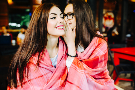 women friends: Two young and beautiful girls share secrets in cafe Stock Photo