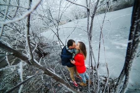 frozen river: beautiful couple posing near a frozen river in the park Stock Photo