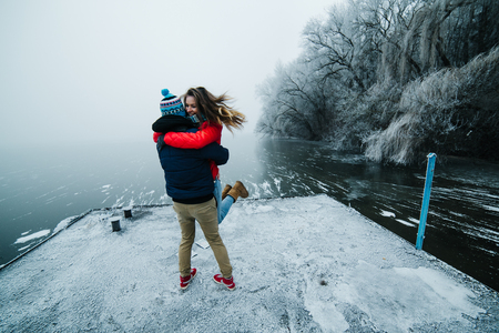 couple having fun: beautiful couple having fun on the pier at the lake