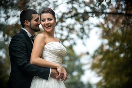 parejas amor: novio abraza suavemente a la novia con un ramo de detrás en un parque