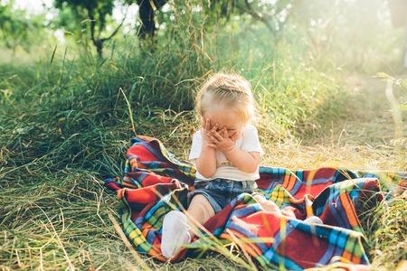 klein meisje zit alleen op het grasveld