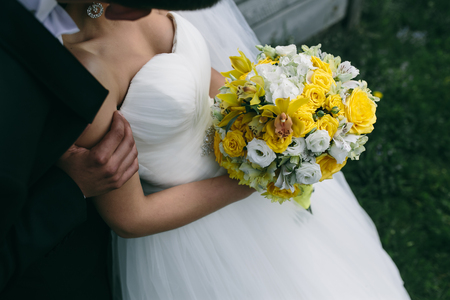 Photo wedding bouquet in hands of the bride on the nature Banque d'images
