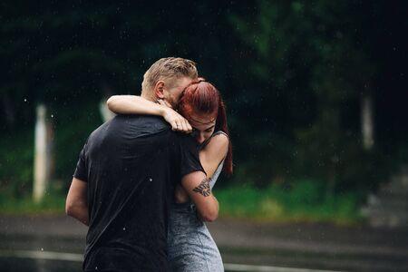 bella pareja abrazos en el exterior bajo la lluvia