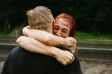 UOMO pioggia: bella coppia abbracciare al di fuori sotto la pioggia