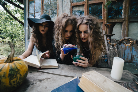 Three vintage witches perform magic ritual, at the table, with the elixir in hand on the eve of Halloween