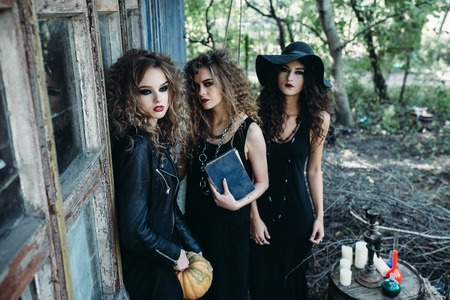 witch: three vintage women as witches, poses near an abandoned building on the eve of Halloween