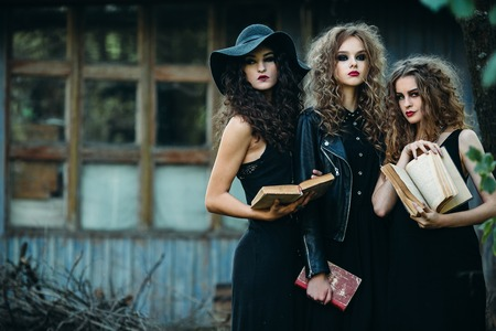 three vintage women as witches, pose in front of an abandoned building with books in hand on the eve of Halloween