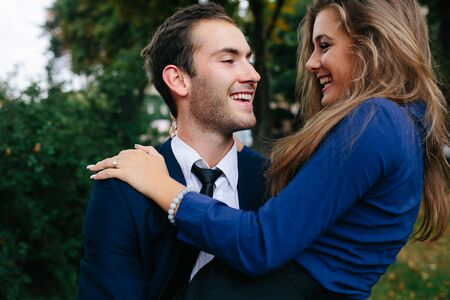holding close: man holding his girlfriend in his arms in the park, close angle Stock Photo
