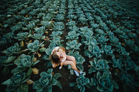 Mom and daughter having fun on the field with cabbage Stockfoto