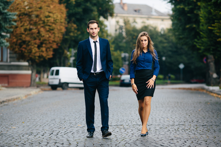 sexy couple black background: man and woman walking together on the street Stock Photo