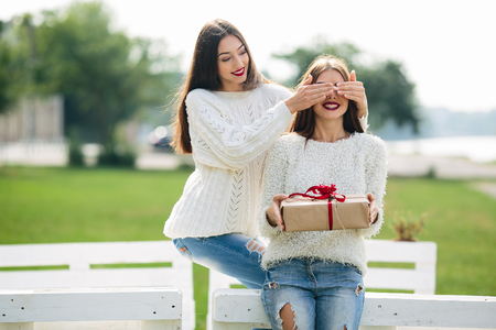closes eyes: girl closes eyes with her hands the other girl with a gift
