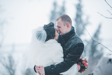 bride and groom background: Bride and groom walking on the European city in the snow Stock Photo