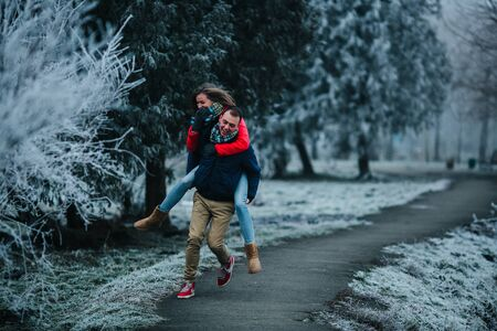carries: man carries his girlfriend on his back in the park