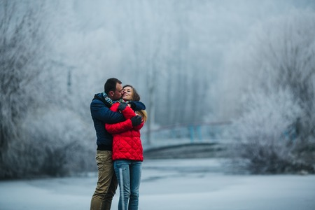 couple nature: beautiful couple posing near a frozen river in the park Stock Photo