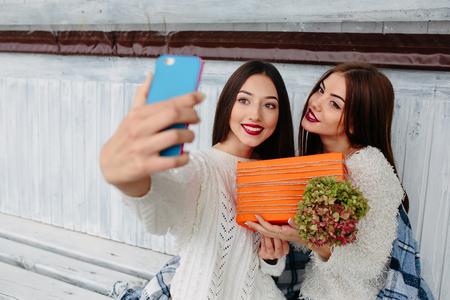 make a gift: Two girls sit on a bench outside and make selfie with gift