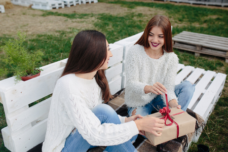 unpack: Two beautiful girls sitting on a bench and holding in their hands gifts