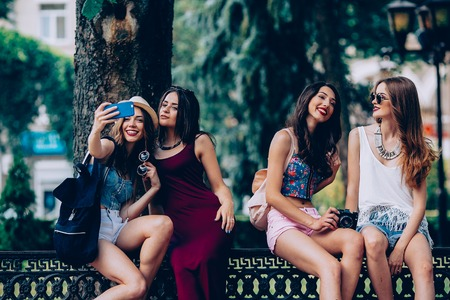 fashion clothing: four beautiful young girls make selfie in the park