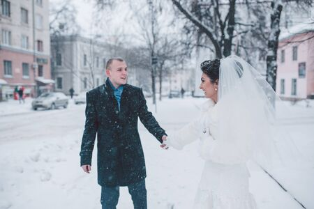 winter wedding: bride and groom in a winter frost with a snowflow