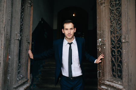 opens: handsome young man opens an old door Stock Photo