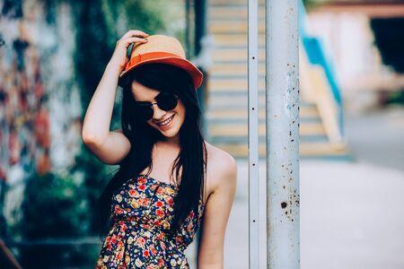 belle brunette: belle fille dans des lunettes de soleil posant pour la cam�ra dans la ville