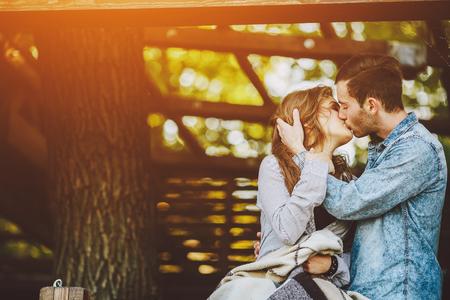 Jeune couple amoureux enveloppé en plaid debout et embrassant